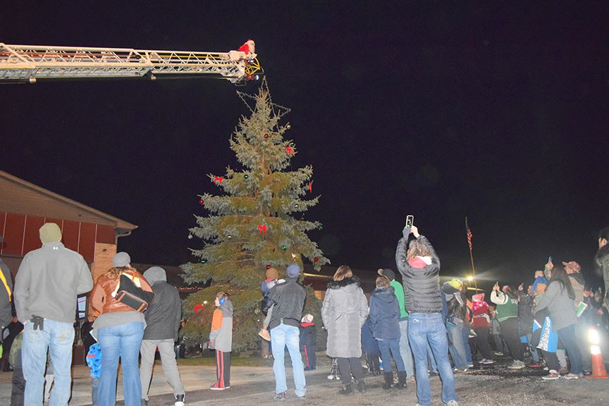 Santa climbs ladder of fire truck to light the tree